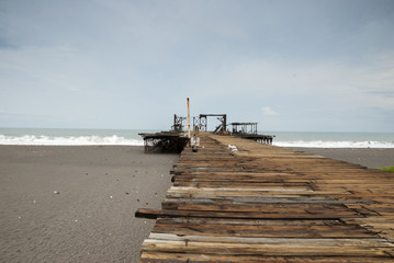 Old rusty pier in Guatemala shot in a cloudy morning. Champerico