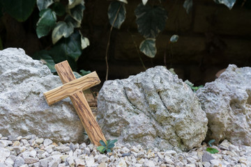 wooden cross against stones