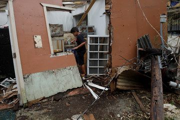 Ian Rodriguez Rivera cleans up the area of a home damaged by Hurricane Maria near the municipality of Orocovis, outside San Juan