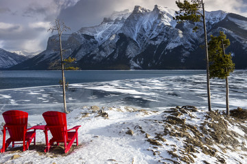 Red Adirondack Chairs and distant snowy mountain tops Landscape at Lake Minnewanka on cold winter day in Banff National Park, Rocky Mountains Alberta Canada