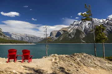 Red Adirondack Chairs and distant snowy mountain tops Landscape at Lake Minnewanka on sunny summer day in Banff National Park, Rocky Mountains Alberta Canada