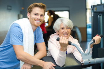 senior woman exercising with fitness instructor inside the gym