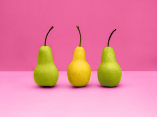 Pears Pop art Two green and one yellow pears are standing upright in a row on pink background Trendy still life with fruits