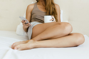 Woman in the bed reading smartphone and drinking coffee