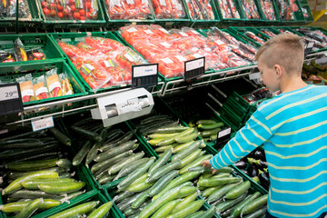 young boy shopping and choosing organic vegetables
