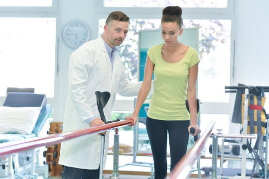male physiotherapist teaching female patient to walk