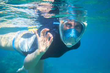 Snorkel girl underwater shows ok gesture. Snorkeling in full face mask.