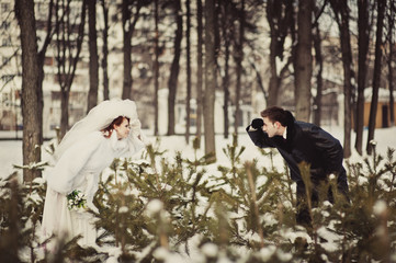 A beautiful ginger bride in a white fur coat and a groom are looking to each other behind the branches in the snowy park. Winter wedding outdoors.