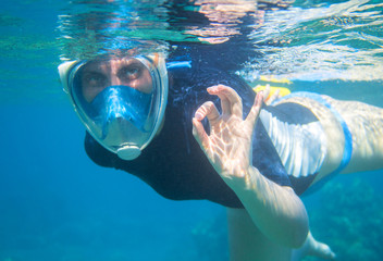 Woman snorkeling in blue water shows ok by fingers. Snorkeling in full face mask.