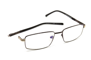 Broken optic glasses on white background. Eye glasseswith thin metal rim after accident.