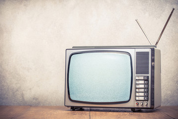 Retro old analog TV set receiver with monochrome static noise on display front textured concrete wall background. Television broadcasting concept. Vintage style filtered photo
