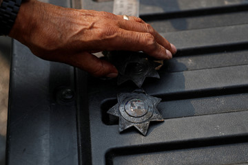 Retired officer Tom Francois places his officers' badges recovered amongst the ruins of his home destroyed by the Tubbs Fire in Santa Rosa, California