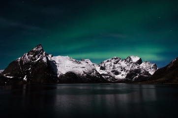 Polar light above the sea and mountains on the Lofoten Islands