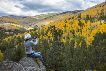woman taking picture with cell phone of beautiful mountains covered in fall colors