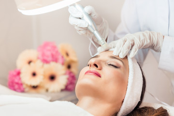 Close-up of the face of a woman relaxing during non-surgical facelift treatment in a contemporary beauty salon with innovative technology