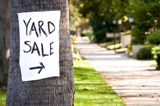 Hand painted yard sale sign with direction nailed to a palm tree.
