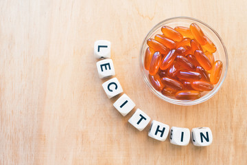 Lecithin gel pills in a round glass bowl and with the word Lecetin from the letters of cubes on a light wooden background. Soy and sunflower lecithin benefits for skin, digestion, lower cholesterol.