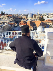 Jerusalem, Israel - 04 March, 2017: Priest sitting with view on rooftops of Old City of Jerusalem. Grey dome of Church of Our Lady of the Spasm (Armenian church) and golden Dome of the Rock