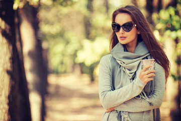 Beautiful  girl in stylish fashion clothes in autumn Park.