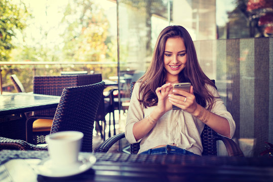 woman in cafe drinking coffee and using her mobile phone