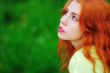 Cute red-haired girl resting on the green lawn and looks to side, closeup.