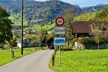 Autostrasse vor Dorf mit Ortsschild der Gemeinde Giswil im Kanton Obwalden, Schweiz