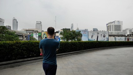Man walks down the street and photographs on the smartphone. Man making photo with his mobile on the street. Young man photographing on the street