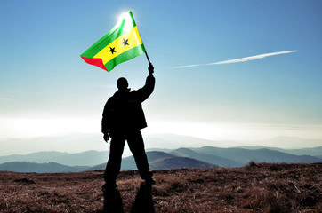 Successful silhouette man winner waving Sao Tome and Principe flag on top of the mountain peak
