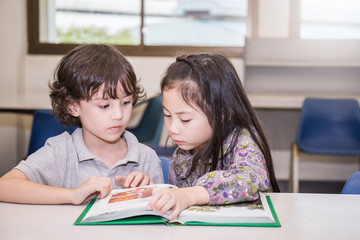 Two young children reading books at the school library, Education concept