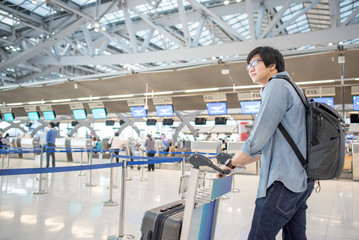 young asian waiting for check in and drop his luggage at airline check-in counter inside the international airport terminal, travel lifestyle concept
