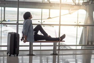 Young Asian man sitting on bench in the airport terminal with suitcase luggage, travel lifestyle