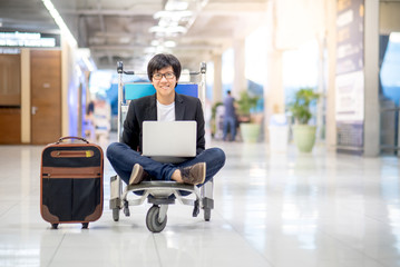 Young asian man working on trolley in airport terminal