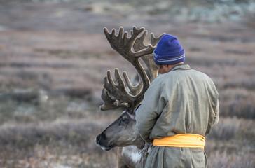 tsaatan man, dressed in a traditional deel, with his reindeers