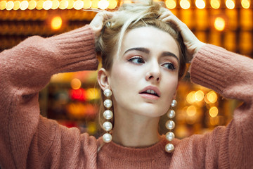 A beautiful young blonde woman dressed in a large warm pink sweater with gorgeous earrings made of big pearls.