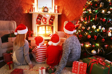 happy family celebrating Christmas near the fireplace under the Christmas tree