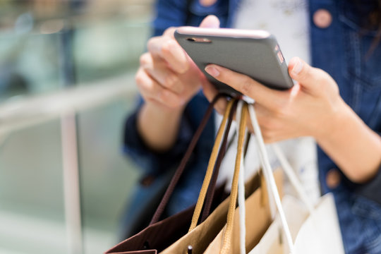 Close up of woman using cellphone and holding shopping bags