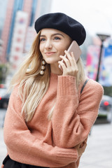 A beautiful young blonde woman dressed in a large warm pink sweater with a black beret and gorgeous earrings. Talking with friend on her pink smartphone in a big spectacular Chinese city in autumn.