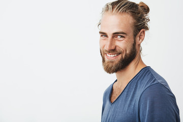 Happy young bearded guy with fashionable hairstyle and beard looking at camera, brightfully smiling with teeth, being happy about day off on work. Wall mural