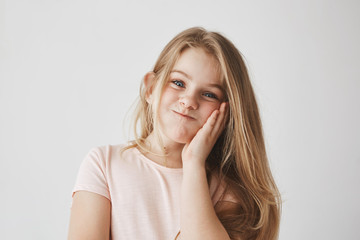 Funny little girl with beautiful long blonde hair looking in camera, squeezing cheek with hand, making funny face expressions, having fun..