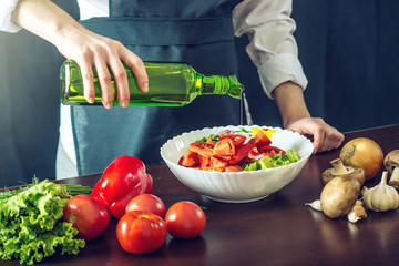 The chef in black apron makes a vegetable salad. Concept of eco-friendly products for cooking
