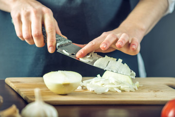 The chef in black apron cuts an onion with a knife. Concept of eco-friendly products for cooking