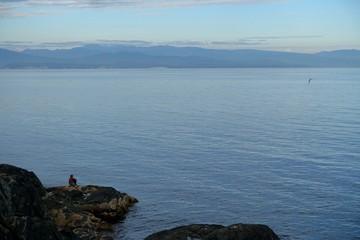 Einzelne Frau im Hintergrund betrachtet szenische Aussicht auf Meer und Inseln.