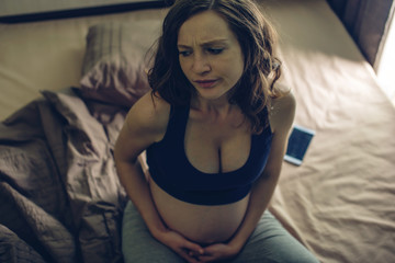 Pregnant woman feeling pain in her belly lying in bed with insomnia at night. Concept of pregnancy and health