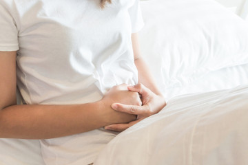 Closeup woman hand holding abdominal with stomach ache lying on bed, health care and medical concept