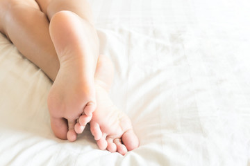 Closeup woman feet relaxing and happy time on white bed, beauty and health care concept
