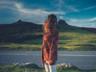 Young woman standing by road in wilderness