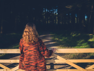 Woman by gate in forest