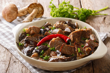 Delicious food: beef stew with wild mushrooms in spicy sauce close-up in a bowl. horizontal