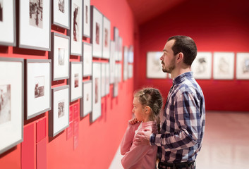 Father and daughter looking at exhibition of photos in museum
