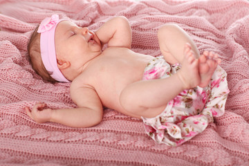 Little lady is lying on the pink woven blanket. Newborn. Family